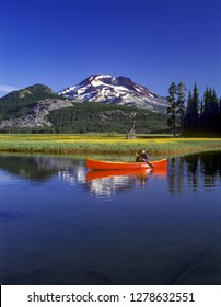 Bend, Oregon - 8/6/2010:  A man paddling a red canoe on Sparks Lake, Oregon Cascade mountains, Willamette National Forest, Oregon.