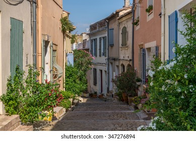 Bended old street with plants and flowers in Arles, France