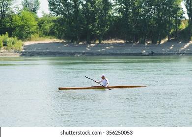 Bendery,Pridnestrove, June 19,2015 Open Championship of rowing. Michael Kutsyn in sport kayak paddles on the water.