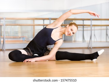 Bending ballet dancer stretches herself on the wooden floor in the classroom