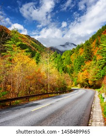 Bending road among colorful fall woods. Scenic mountains in fog are visible on blue sky background. Yellow, orange, red and green trees are growing along road. Amazing autumn landscape.