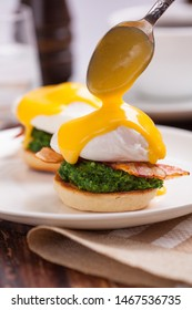 Benedict eggs with spinach. Eggs Florentine. English muffin with poached egg and bacon. Pour Hollandaise Sauce on egg.