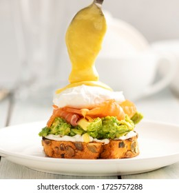 Benedict poached egg with avocado, cream cheese and salmon in hollandaise sauce on bread toast. Pouring from a spoon. Breakfast.