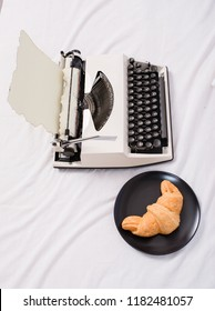 Benefit being writer is comfortable inspiring workplace. Create inspiring atmosphere before start writing new page with typewriter. Typewriter and delicious croissant plate lay white bed sheets.
