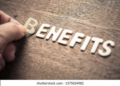 BENEFITS, closeup hand place a wood letter into the word for benefits concept