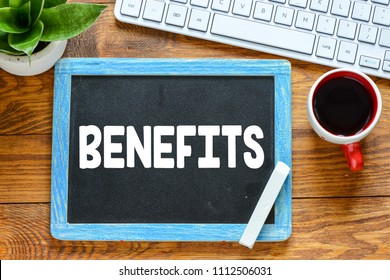 BENEFITS handwritten with white chalk on a blackboard on wood background