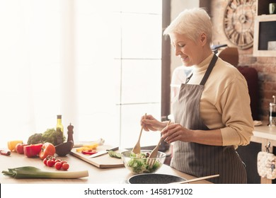Benefits of healthy nutrition. Positive senior lady cooking fresh salad at kitchen, empty space