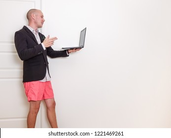 The benefits of video conference / videotelephony. Man wearing suit jacket and orange shorts, holding a laptop computer.