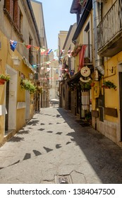 Benevento, Campania / Italy - 07 20 2018: An alley shows the character of the historical center of Benevento. Triangular country flags and flowers and plants cheer up this beautiful place.