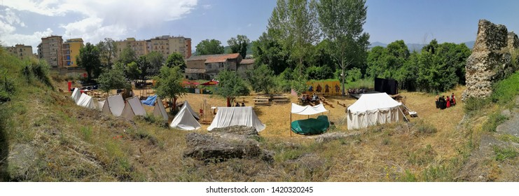 """Benevento, Campania, Italy - June 9, 2019: Panoramic photo of the historical re-enactment of a Lombard village in the archaeological area of the Saints Quaranta during the eighth edition of the """"La Co"""