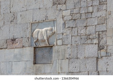 Benevento, Campania, Italy - October, 2018 - Ancient stone sculpture, with ancient Roman inscription, on the steeple of the cathedral of Santa Maria d'Episcopio, Benevento, Italy