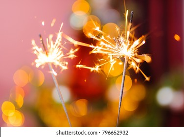 Bengal fire, abstract blur sparklers and colorful bokeh, new year tree background.