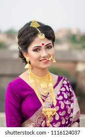 Bengali bride dressed in Indian bridal saree smiling on rooftop Indian lifestyle