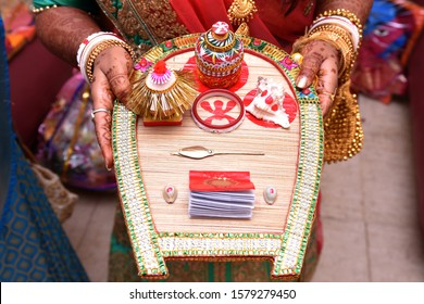 Bengali bride holding wedding accessories or Traditional Wedding Invitation card including sindoor box in Indian wedding
