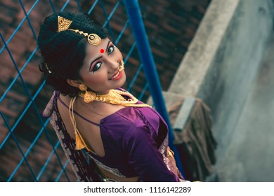 Bengali bride is looking back while descending from the stairs Indian lifestyle