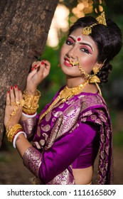 Bengali bride is posing by holding a tree in evening light Indian lifestyle