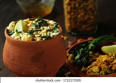 Bengali traditional street food and evening snack, Jhalmuri, in a earthen pot is placed on a wooden surface while its ingredients are arranged in a earthen plate. The glass jar containing the mixture.