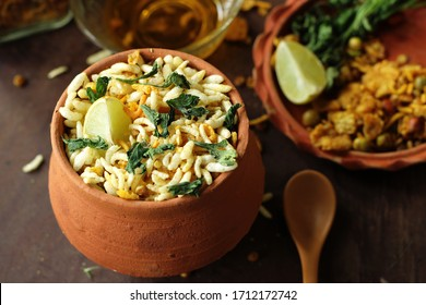 Bengali traditional street food and evening snack, jhalmuri, is placed on a wooden surface with all its ingredients being arranged on a earthen plate. the Indian street food is served in earthen pot.
