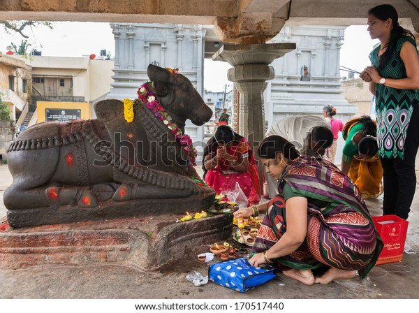 BENGALURU, INDIA - CIRCA NOVEMBER 2013: Women worship, pray, pooja, donate food and light oil lamps in front and around the Nandi statue at Sri Naheshwara Temple in Bangalore.