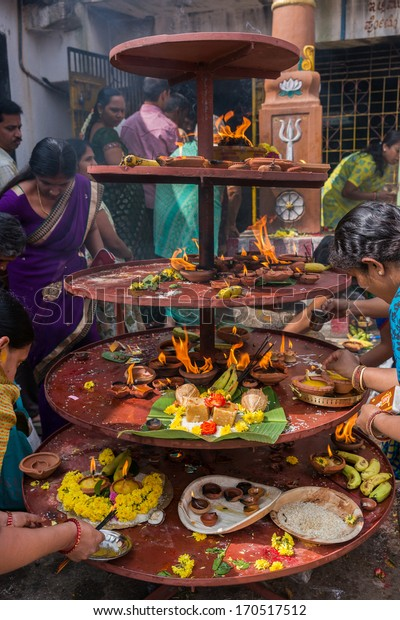 BENGALURU, INDIA - CIRCA NOVEMBER 2013: Women light oil lamps and offer flowers and food at the Sri Naheshwara Temple.