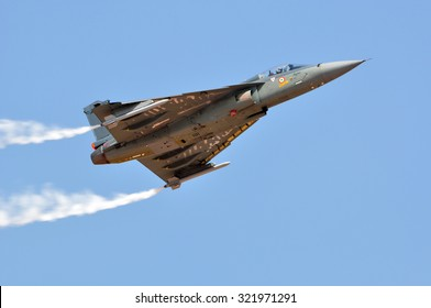 BENGALURU, INDIA - FEBRUARY 22, 2015: HAL Tejas of Indian Air Force performing aerobatic maneuver with smoke trails at Aero India 2015. Aero India is a biennial air show and aviation exhibition.