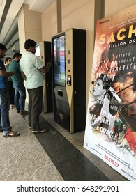 "Bengaluru, India: May 27th, 2017, Man buying ticket from self service kiosk at  at PVR Cinemas, Poster of movie: ""Sachin: A Billion Dreams"" is also in the picture"