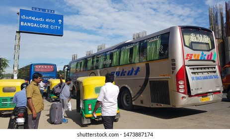 Bengaluru, Karnataka / India - August 08 2019: People alighting from an interstate bus at a busy road with a hoarding that has 'Bangalore City' written in Kannada text