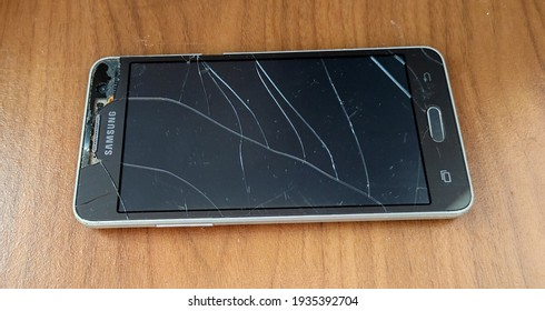 BENGKALIS, INDONESIA - MARCH 13th, 2021 - Broken Samsung Mobile Phone With Brand Samsung Galaxy Grand Prime SM-G530H On Brown Wood Table