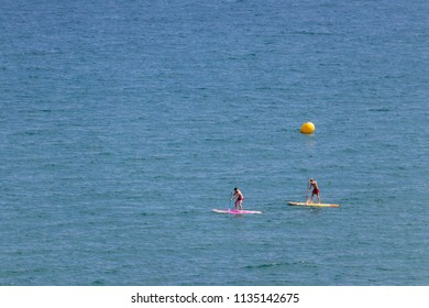 BENICASIM - JULY 2018: People doing SUP (Stand up paddle) paddle surfing on the beach.