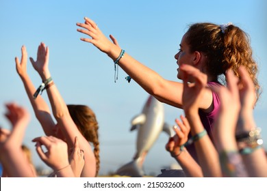 BENICASSIM, SPAIN - JULY 20: Young woman from the crowd cheering at FIB Festival on July 20, 2014 in Benicassim, Spain.