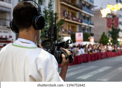 Benidorm, Spain, 07/26/2018; Videographer with a camera in his hands shoots city holiday. Journalist at work. Video filming.