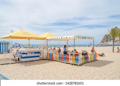 Benidorm, Spain - 16 June, 2019: View to Benidorm Poniete beach. People resting in the beach, relaxing, reading in public Benidorm Poniente Beach Library area