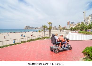 Benidorm, Spain, 17 June, 2019: Senior couple on mobility scooter enjoying summer vacation in Benidorm, Spain