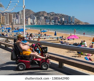 Benidorm, Spain - April 13th 2019: A couple on mobility scooters sitting along the promenade on Levante Beach in the famous city of Benidorm in Spain.