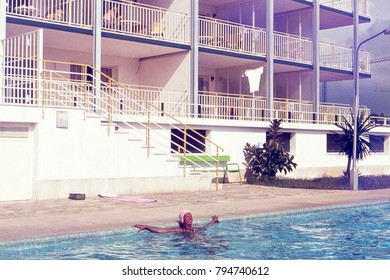 BENIDORM, SPAIN. CA. 1962. Woman enjoying the sun in a swimming pool in front of a 1950´s holiday apartment building.