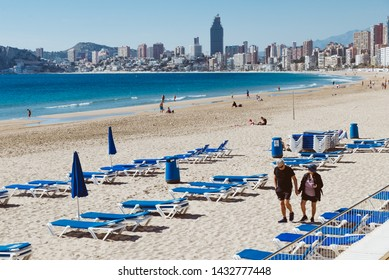 Benidorm, Spain- february 19, 2019: mature couple is having a walk hand in hand on Playa Poniente, a very long sandy beach in Benidorm, a well known spanish seaside destination.
