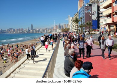 Benidorm, Spain. March 09, 2018. Holidaymakers and locals mingle on the promenade and exercise on the Poniente beach at Benidorm on the Costa Blanca in Spain.