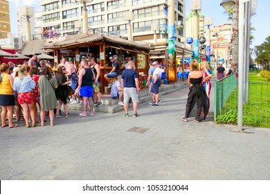 Benidorm, Spain. March 10, 2018. Holidaymakers gather for social food and drinks during the daytime at the Tiki beach bar on the promenade at Benidorm on the Costa Blanca in Spain.