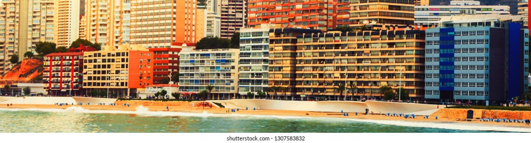 Benidorm, Spina. Summer resort Benidorm, Spain with beach and famous skyscrapers in the evening. Colorful cloudy sky