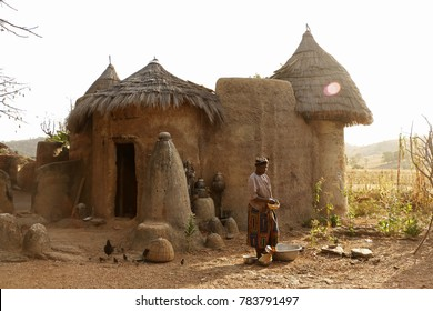 Boukoumbé Benin December 20 2014 Tammari woman feeds ducks in front of her mud house