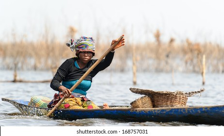 BENIN, MARCH 9, 2012: Unidentified Beninese girl rows the boat over the river in Benin, Mar 9, 2012. People of Benin suffer of poverty due to the unstable economical situation