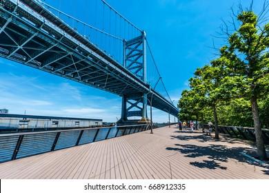 The Benjamin Franklin Bridge Towers high over the Delaware River and the Race Street Pier in Philadelphia, Pennsylvania.