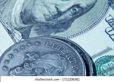 Benjamin Franklin face on one hundred US Dollar bill and coin with description: Liberty as symbol: America - the land of opportunities and freedom. Selective focus on coin.