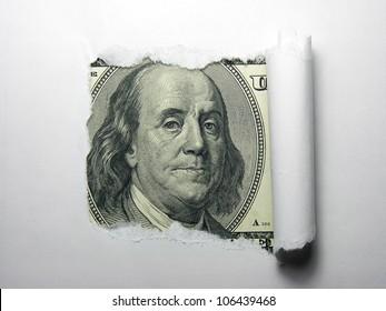 Benjamin Franklin macro peeking through torn white paper.