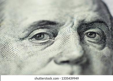 Benjamin Franklin's look on a hundred dollar bill. Benjamin Franklin portrait macro usa dollar banknote or bill. Selective focus.