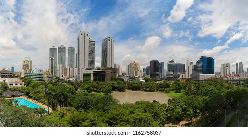 Benjasiri park in Sukhumvit district. Panorama of financial district and skyscraper buildings in Bangkok city with blue sky. Downtown at noon, Thailand.