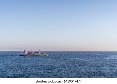 Benoa Bay, Bali, Indonesia - February 26, 2019: Gray red Meratus Sabang General Cargo Ship sails on Benoa bay. Darker blue sea water and light blue evening sky. Colored containers on deck.