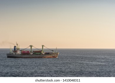 Benoa Bay, Bali, Indonesia - February 26, 2019: Gray red Meratus Sabang General Cargo Ship sails on Benoa bay during sunset. Darker blue sea water and twilight evening sky. Colored containers on deck.