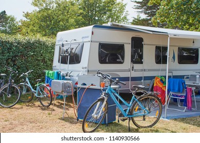 Benodet, Brittany/France - July 01, 2018: Campsite with a Fendt caravan, bikes and camping kitchen on a campsite in Benodet, France.