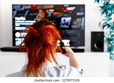 Benon, France - December 30, 2018: Woman sitting in her living room Holding a TV remote control and displays the netflix homepage. Netflix Inc. is an American entertainment company founded on 1997